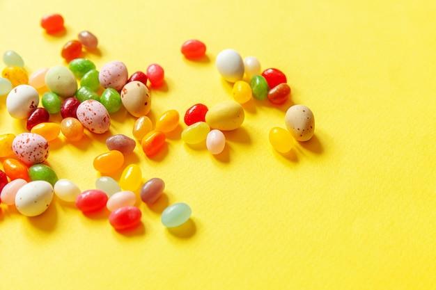 Uova di cioccolato della caramella di pasqua e dolci di gelatina isolati su fondo giallo alla moda