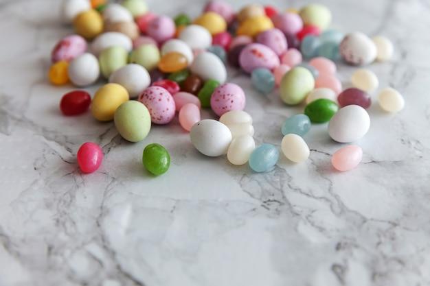 Uova di cioccolato caramelle di pasqua e caramelle di gelatina sulla tavola di marmo grigio alla moda