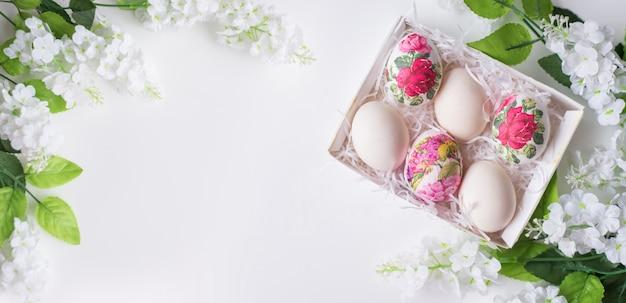 Carta di pasqua. uova con un motivo floreale su uno sfondo bianco con fiori nella tecnica del decoupage. spazio per il testo.