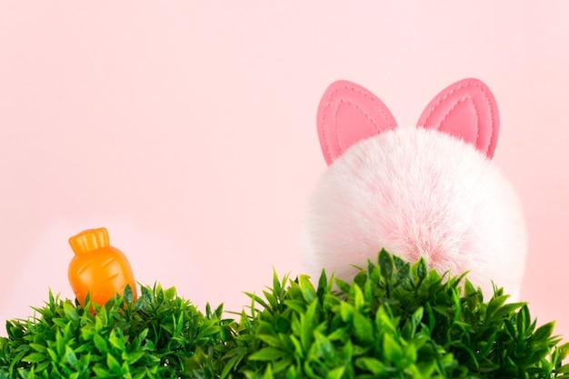 Biglietto pasquale con carota e orecchie da coniglio. progettazione di vacanze di primavera. sfondo di pasqua.