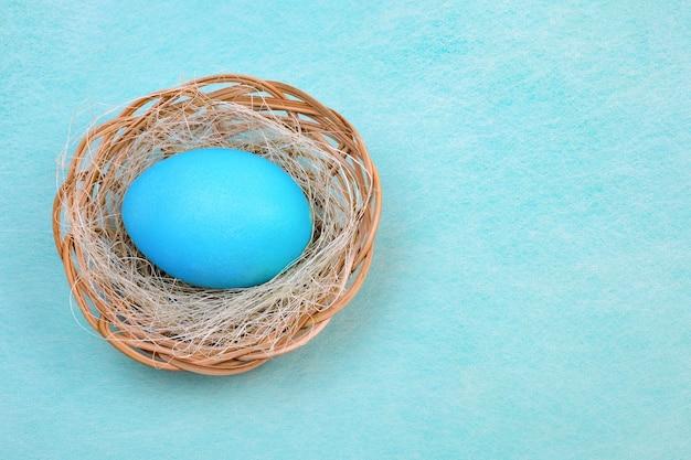 Carta di pasqua con un uovo di pasqua verde acqua in un cesto di vimini sul blu