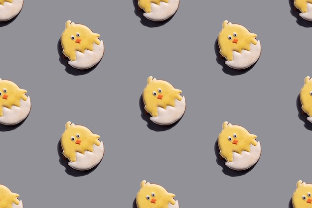 Modello senza cuciture dei biscotti del pollo di pasqua sulla tabella grigia. primavera