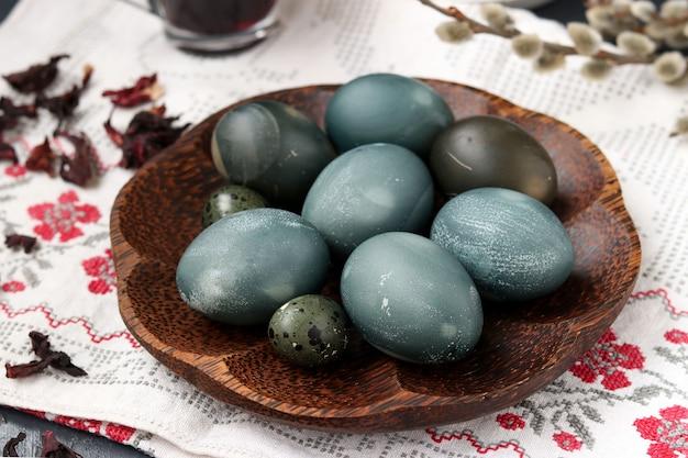 Pollo pasquale e uova di quaglia su un piatto, dipinte con tè dai petali di una rosa sudanese o di ibisco