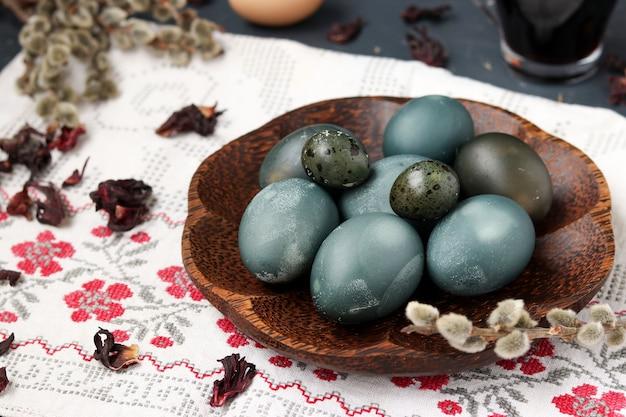 Pollo di pasqua e uova di quaglia su un piatto, dipinte con tè dai petali di una rosa sudanese o ibisco