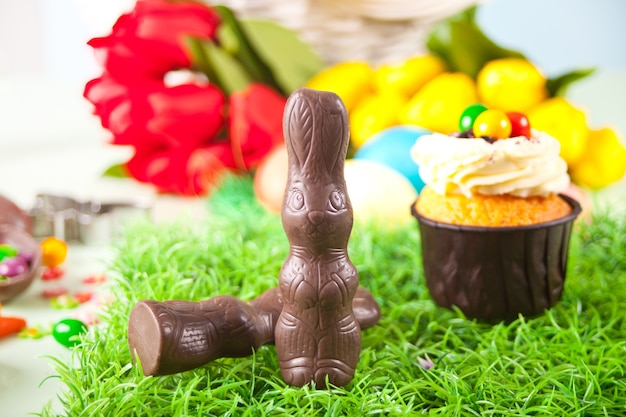 Coniglietto di cioccolato di pasqua, cupcake, caramelle su un tavolo festivo. tulipani in fiore sullo sfondo.