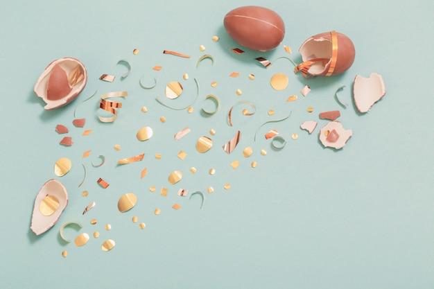 Uovo di cioccolato di pasqua con coriandoli dorati su sfondo blu carta di menta