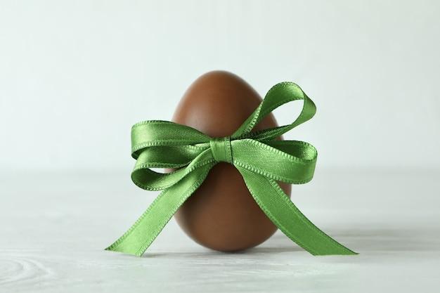 Uovo di cioccolato di pasqua con il nastro verde sulla tavola di legno bianca