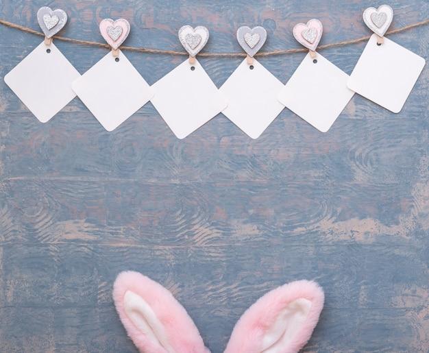 Scheda variopinta di pasqua fatta di ghirlanda vuota e orecchie di coniglietto di pasqua rosa su fondo di legno blu
