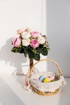 Uova colorate di pasqua in busket bianco sulla tavola di legno. bouquet di fiori di rosa sul tavolo. buona pasqua. atmosfera primaverile.