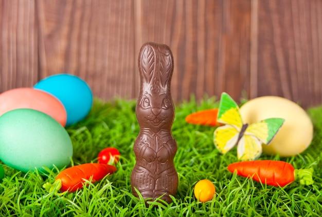 Uova colorate di pasqua, coniglietto di cioccolato, caramelle di carote nell'erba sui precedenti di legno.