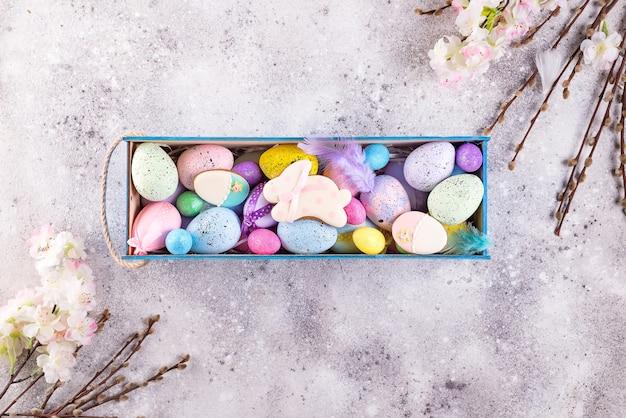 Uova colorate di pasqua dipinte a colori vivaci e coniglietto di biscotti glassato con nido di paglia