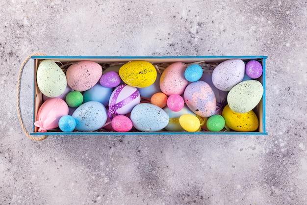 Le uova variopinte di pasqua dipinte nei colori luminosi con la paglia annidano in scatola di legno su fondo di pietra