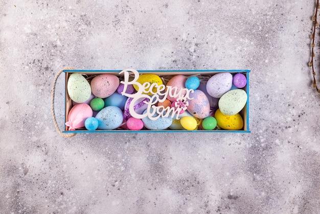 Uova variopinte di pasqua dipinte nei colori luminosi con il testo nelle feste felici ucraine in scatola di legno su fondo di pietra