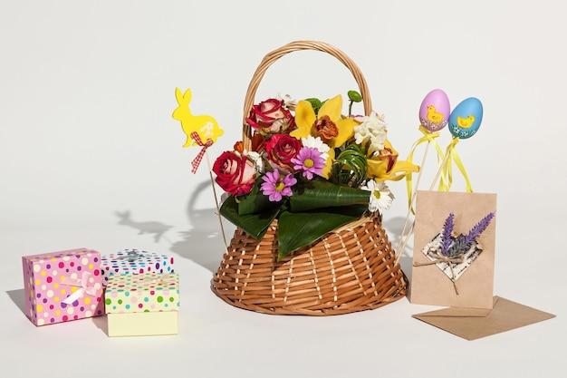 Composizione pasquale. luminosa composizione pasquale di bouquet in cestino, scatole colorate, carte e uova.