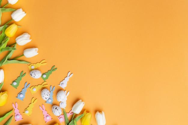 Composizione di pasqua coniglietto tulipani sfondo arancione vista dall'alto copia spazio concetto primavera biglietto di auguri invito
