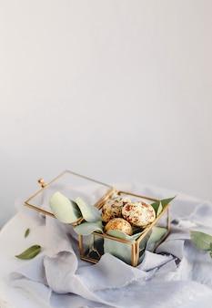 Composizione pasquale. uova di pasqua in una scatola di vetro su nastri di seta e su sfondo bianco e grigio. copia spazio.