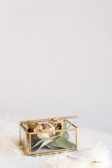 Composizione pasquale. uova di pasqua in una scatola di vetro su uno sfondo bianco e grigio. biglietto di auguri con spazio per il testo.