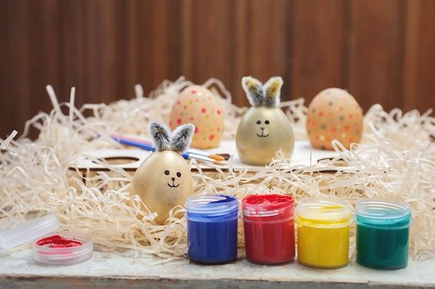 Composizione di pasqua delle uova su una superficie di fieno. creatività dei bambini. dipingere le uova.