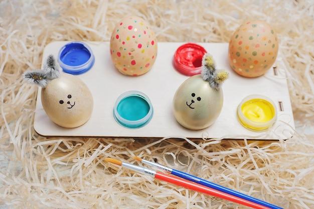 Composizione di pasqua delle uova su una superficie di fieno creatività dei bambini dipingere le uova