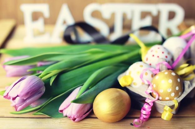 Fiore ed uova della composizione di pasqua su fondo di legno