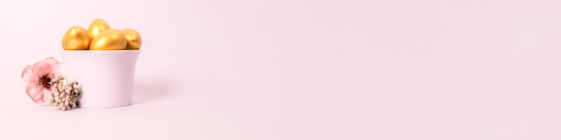 Composizione di pasqua di uova decorative dorate in una tazza di porcellana e un fiore su uno sfondo rosa. messa a fuoco selettiva, copia dello spazio.