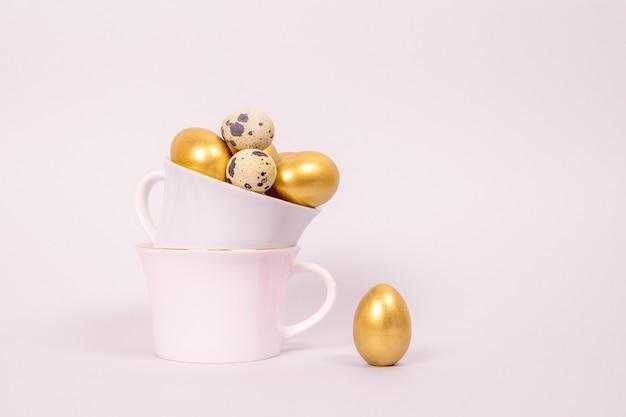 Composizione di pasqua di uova di quaglia e decorative dorate in tazze di porcellana su una rosa