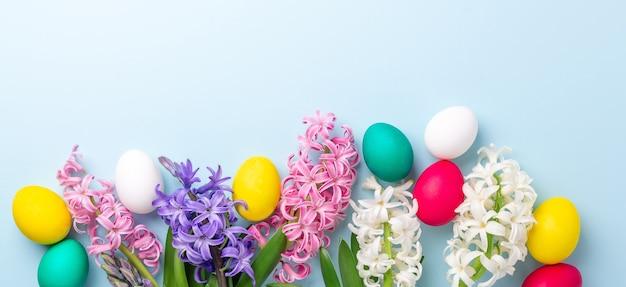 Composizione di pasqua. uova di pasqua multicolori e giacinti su sfondo blu. concetto di pasqua. copia spazio - immagine