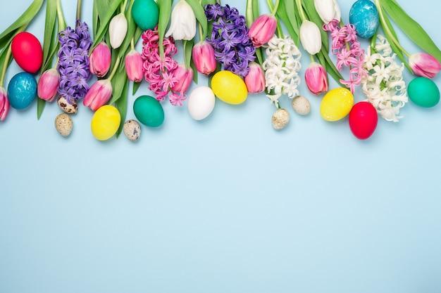 Composizione di pasqua. uova di pasqua multicolori, tulipani e giacinti sul tavolo blu. concetto di pasqua.