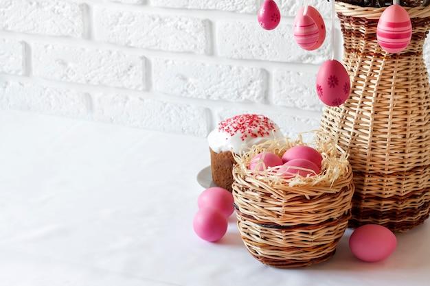 Composizione di pasqua rosa uova colorate nel cesto di vimini e torta di pasqua su sfondo bianco. copia spazio