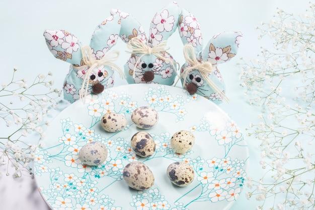 Composizione di pasqua. tre coniglietti pasquali tessili fai-da-te in piedi intorno al piatto con decorazioni floreali primaverili con uova di quaglia su azzurro pastello.
