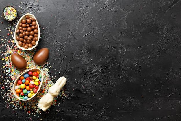 Vista dall'alto della composizione di pasqua. uova di cioccolato con caramelle colorate sul muro nero laici piatta con spazio per il testo