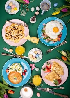 Composizione di pasqua con colazione piatto giaceva con uova strapazzate bagel, tulipani, frittelle, pane tostato con uovo fritto e asparagi verdi, uova di quaglia colorate. vista dall'alto