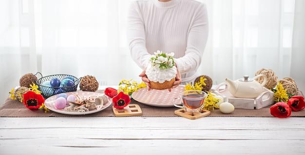 Composizione di pasqua con torta in mani femminili, tè, fiori, uova e dettagli di arredamento. pasqua concetto di vacanza in famiglia.