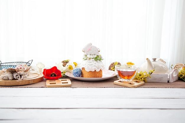 Composizione di pasqua con torta, tè e fiori. il concetto di un festoso tea party.