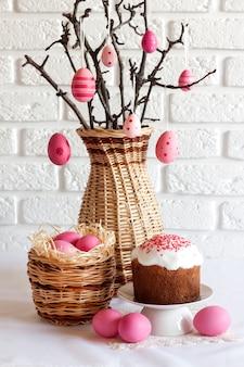 Composizione di pasqua con rami di albero decorati in un vaso di vimini, uova colorate di rosa in cestino di vimini e torta di pasqua