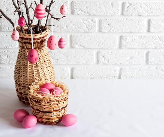 Composizione di pasqua con i rami degli alberi decorati in un vaso di vimini e uova colorate di rosa nel cesto di vimini su sfondo bianco. copia spazio