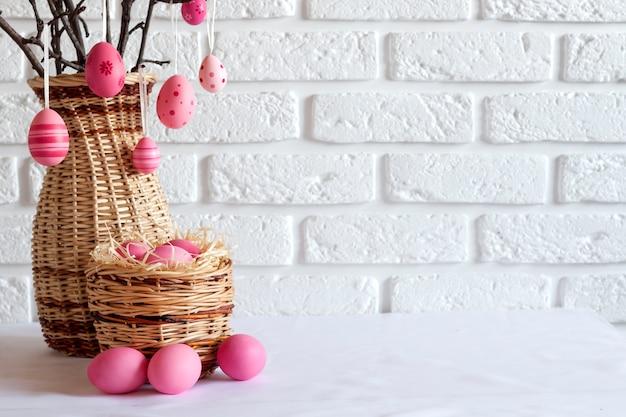 Composizione di pasqua con rami di albero decorati in un vaso di vimini e uova colorate rosa nel cestino di vimini