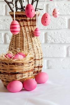 Composizione di pasqua con rami di albero decorati in un vaso di vimini e uova di colore rosa nel cesto di vimini
