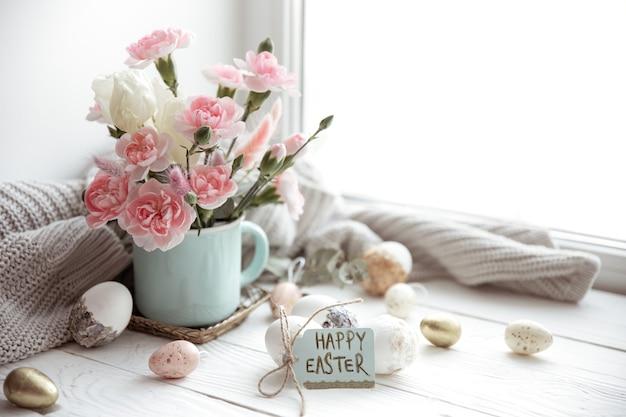 Composizione di pasqua con fiori freschi in un vaso e la scritta buona pasqua sullo spazio della copia della carta.
