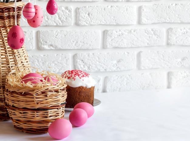 Composizione di pasqua con le uova colorate rosa in canestro di vimini e dolce di pasqua