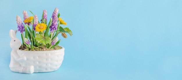 Composizione di pasqua con coniglio e fiori di primavera con lo spazio della copia