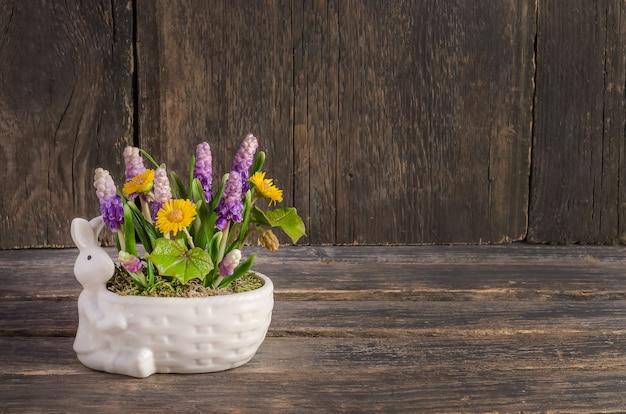 Composizione di pasqua con coniglio e fiori di primavera su un tavolo di legno con spazio di copia