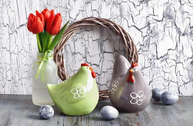Composizione di pasqua con tulipani rossi, galline in ceramica e uova di pasqua su legno