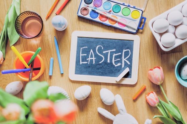 Composizione di pasqua con strumenti per dipingere uova e fiori sulla tavola di legno. vista dall'alto.
