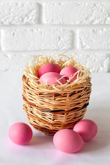 Composizione di pasqua con cesto di vimini e uova colorate di rosa