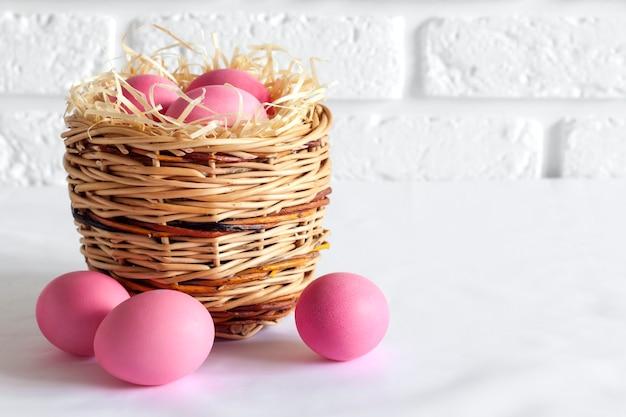 Composizione di pasqua con cesto di vimini e uova di colore rosa