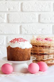 Composizione di pasqua con cesto di vimini con uova colorate di rosa e torta di pasqua decorata