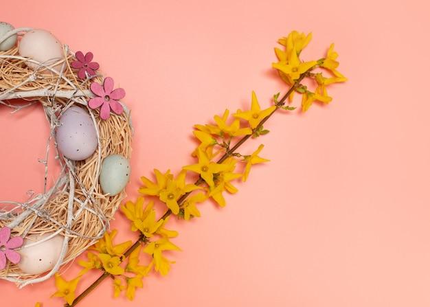 Composizione pasquale di ghirlanda con uova decorative e un ramo di fiori gialli
