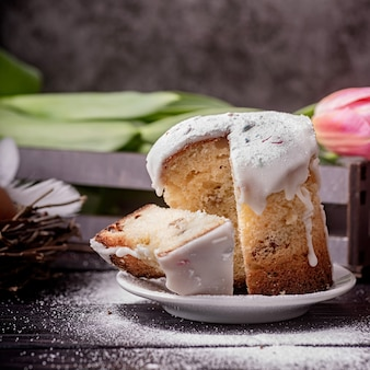 Concetto di pasqua. cuocere e cucinare. torta di pasqua smaltata con i tulipani su fondo rustico scuro