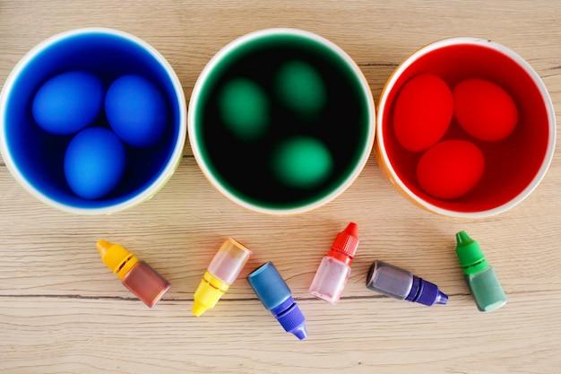 Concetto di pasqua. colorazione delle uova di pasqua decorare le uova di pasqua. tazze con vernice colorata liquida brillante e uova e vernici in bottiglia